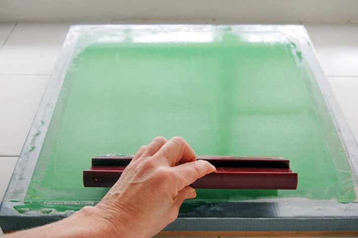 Spreading a thin coat of photo emulsion across silk with a squeegee.