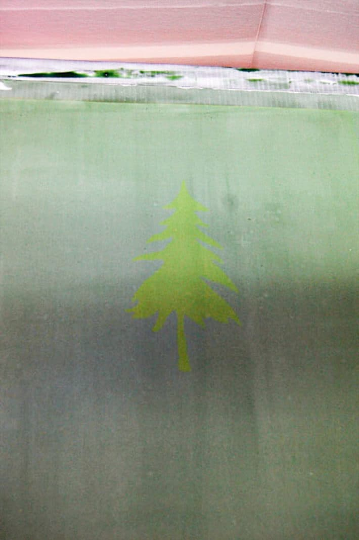 Newly burned screen printing frame with a faint pine tree silhouette.