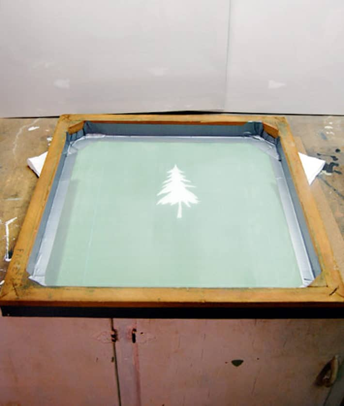 Screen printing frame with tree image laid on top of t shirt ready for paint..