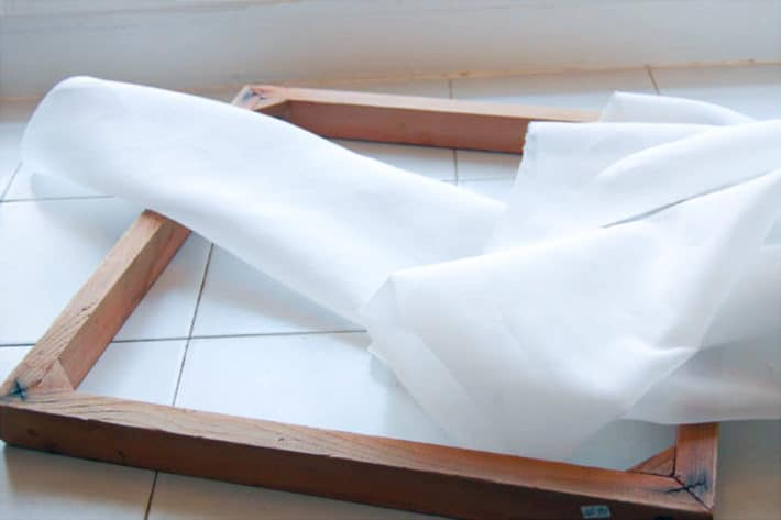 Square wood frame on a white tile counter with sheer white fabric clumped to the side.