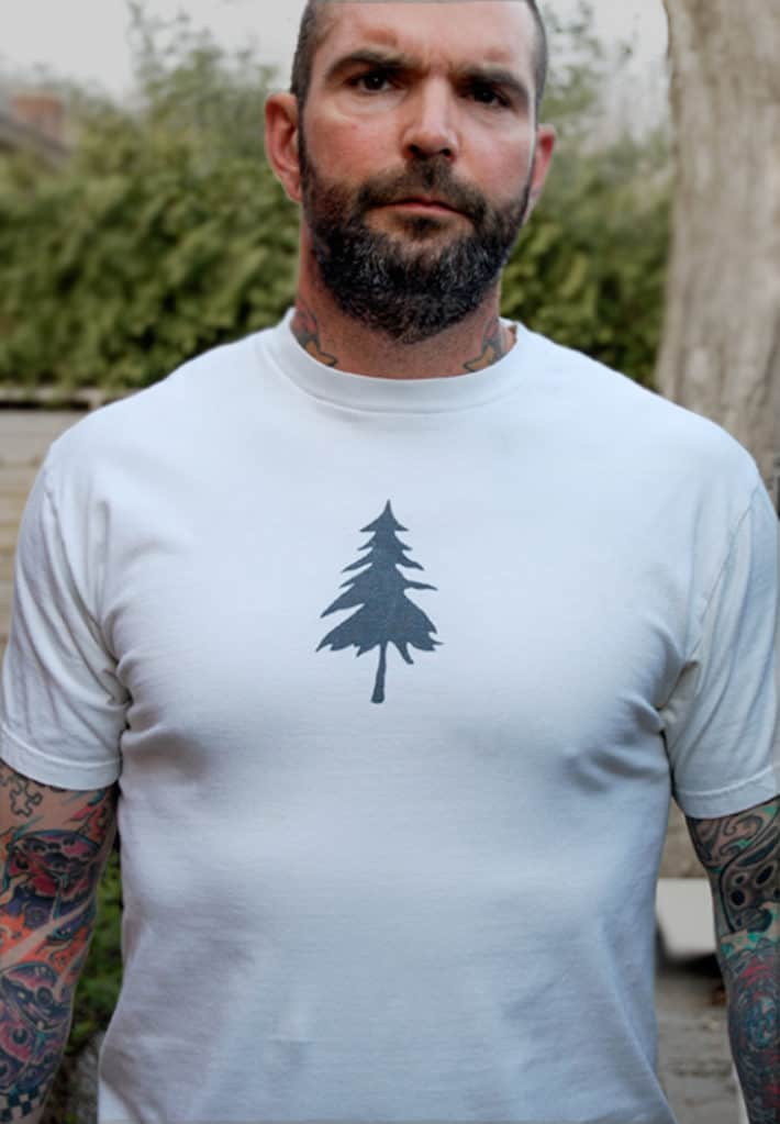 Tattooed man wearing a white tee shirt with the silhouette of a pine tree on it.