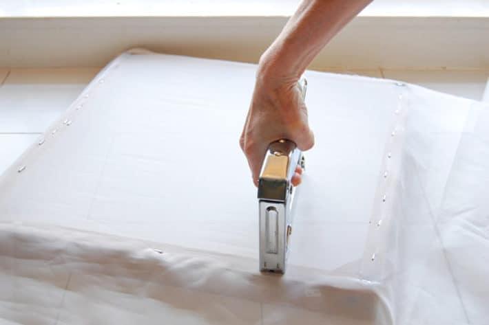 Stapling white sheer fabric onto back of wood frame.
