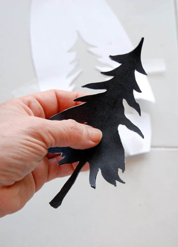 Print of a black pine tree cut away from white printer paper.