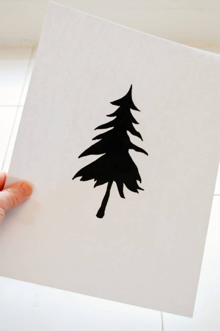 White paper printed with a solid silhouette of a pine tree on it.