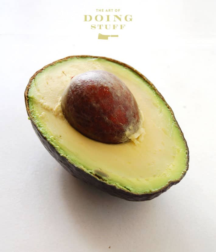 Half an avocado with pit on a white background.