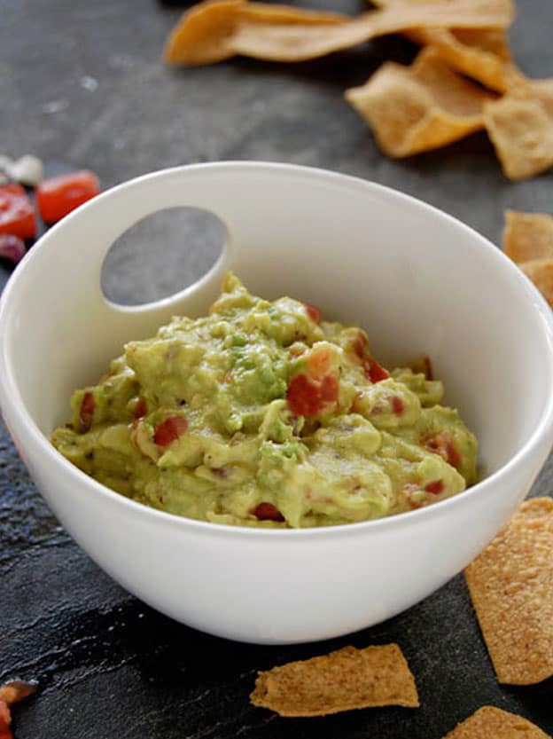 Homemade guacamole with avocado, tomatoes and red onions in a white bowl on a black stone counter.