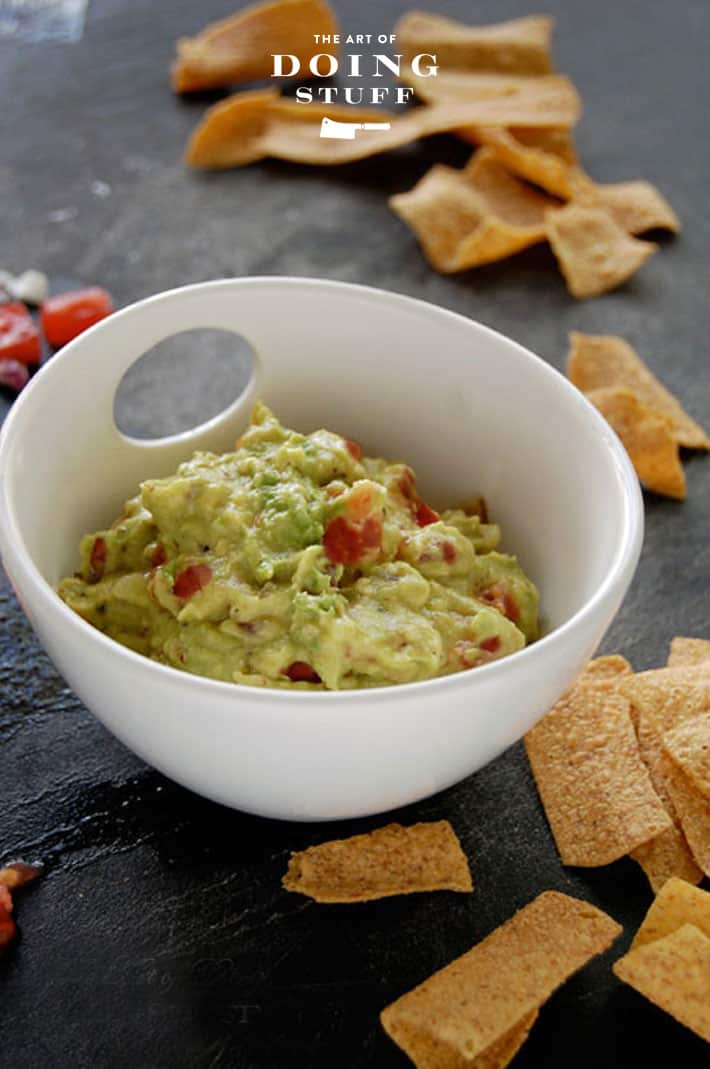 Small white bowl filled with homemade guacamole surrounded by pita chips on a black stone counter.