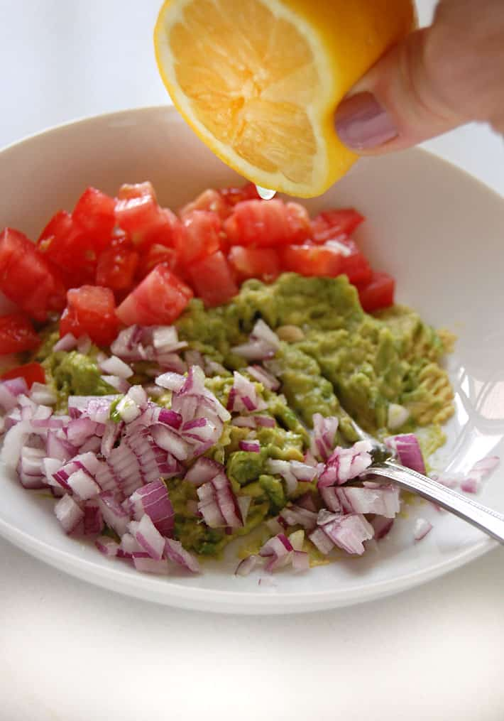 Squeezing lemon into a white bowl of prepped guacamole ingredients.