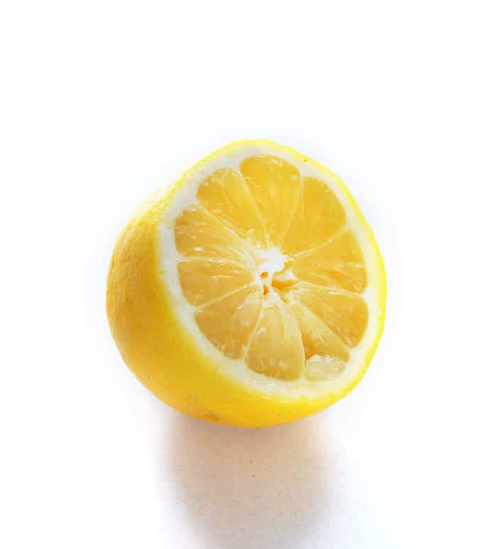 Half of a bright yellow lemon on a white background.
