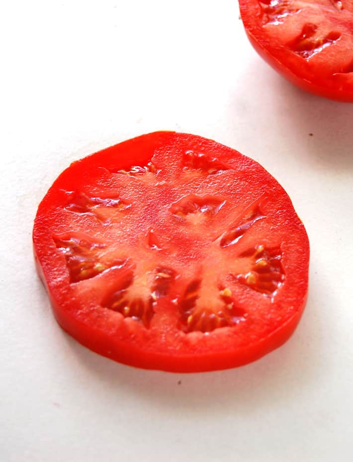 One slice of red tomato on a white backdrop.