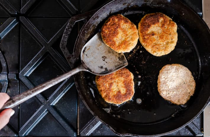 Golden brown chicken burgers pan frying in a cast iron skillet.