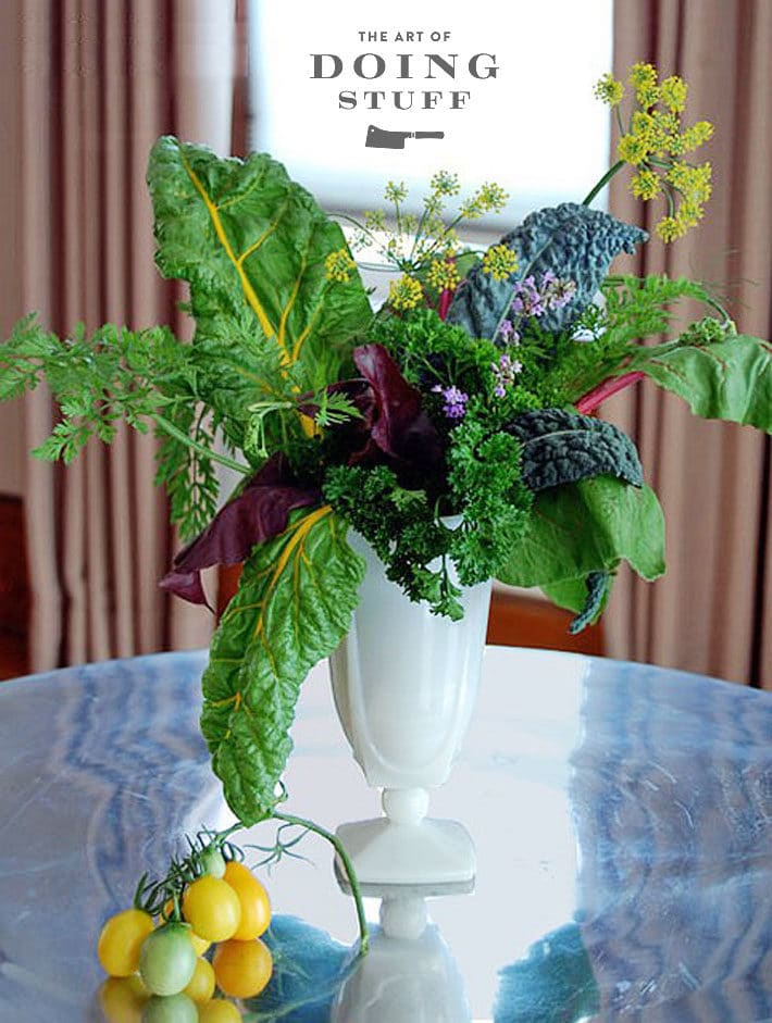 White milkglass vase with an arrangement of vegetables including chard, kale, beet greens, carrot tops and tomatoes.