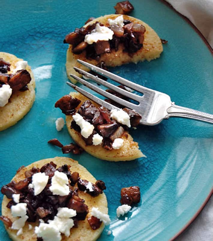 Rounds of pan friend polenta with mushroom topping and goat's cheese on a bright blue plate.