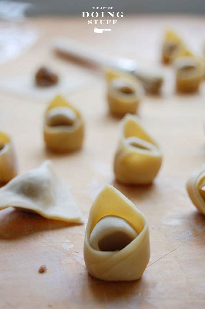 Wood counter scattered with homemade tortellini.
