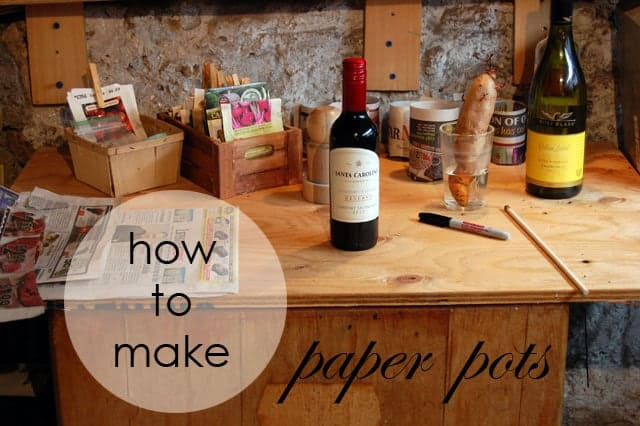 Plywood table covered with seed starting supplies, newspaper and bottles of wine!