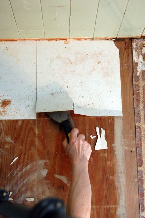Scraping up vinyl tile from plywood with putty knife.