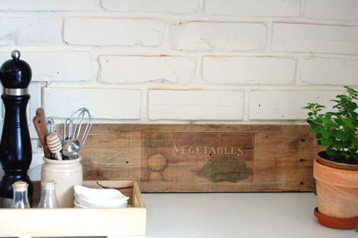 Raw wood with image of vegetables printed on it leaning against white brick wall in farmhouse kitchen.