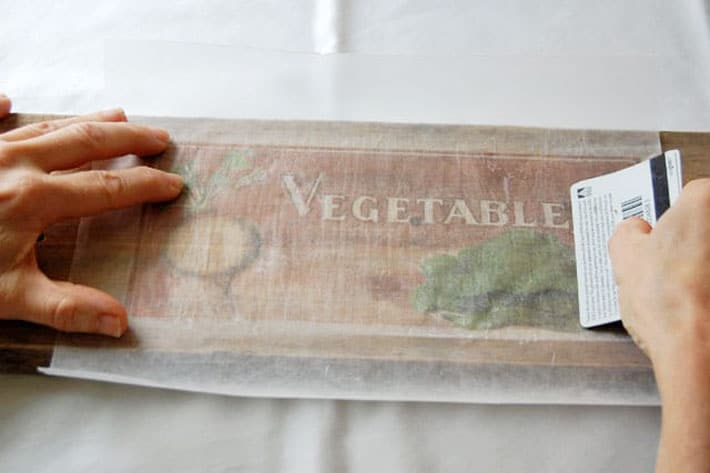 Running credit card over wax paper to rub ink into wood.