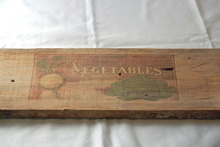 Raw wood with perfect image of the word Vegetables and primitive images of a turnip and cabbage.
