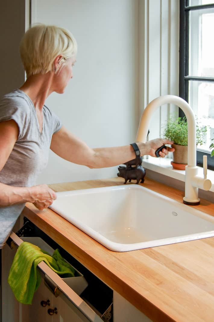 Karen Bertelsen reaches for a plant in her white kitchen with butcher block counter tops.