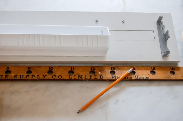 Installing the plastic tray onto the back of a cupboard's false front.