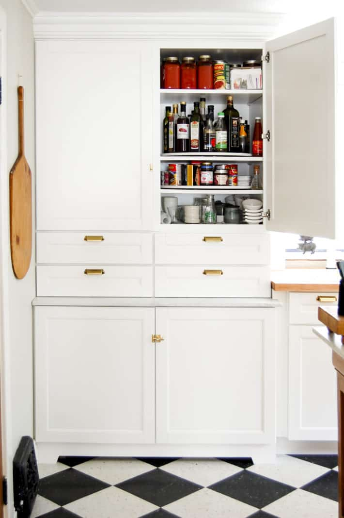 Martha Stewart cupboards from Home Depot stacked like a pantry, with one door open revealing DIY lazy susans inside.