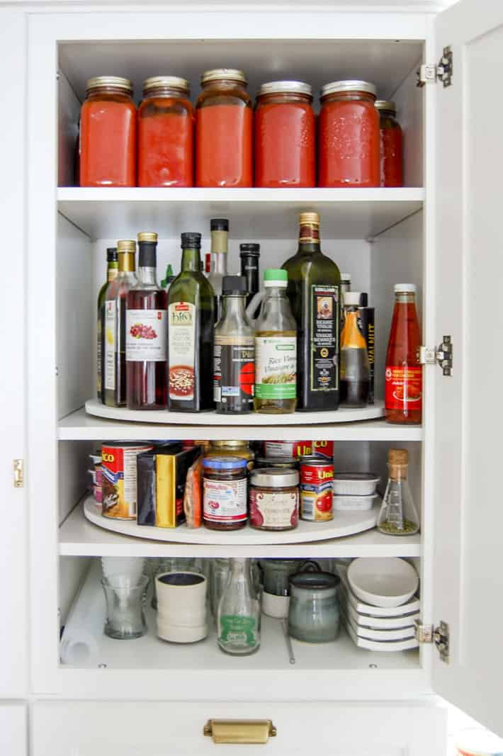 White Martha Stewart pantry cupboard opened to reveal shelves with lazy susans filled with canned and bottled goods.