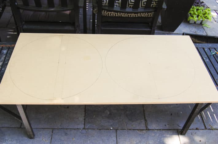 2x4 foot panel of MDF laid on outdoor table with circles marked on it ready for cutting.