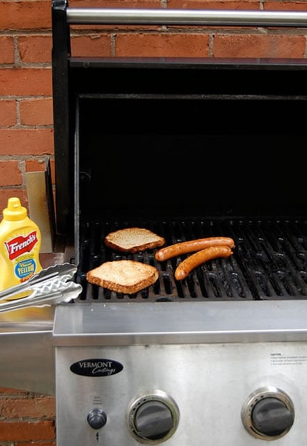 2 hotdogs cooking on a BBQ with a bottle of French's mustard to the side.