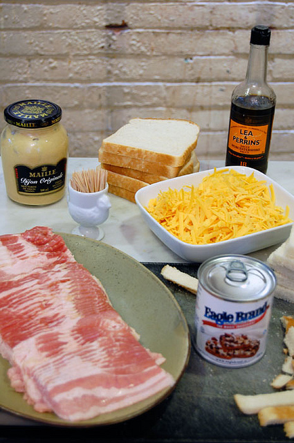 Bacon slices on a green plate surrounded by a a bowl of cheese, bread slices, dijon mustard and other ingredients.
