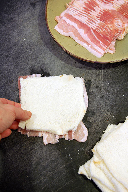 Overhead shot of placing a slice of flattened bread on 3 short, side by side strips of bacon.