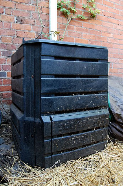 A standard black, square compost bin provided by many municipalities sits against a brick wall.