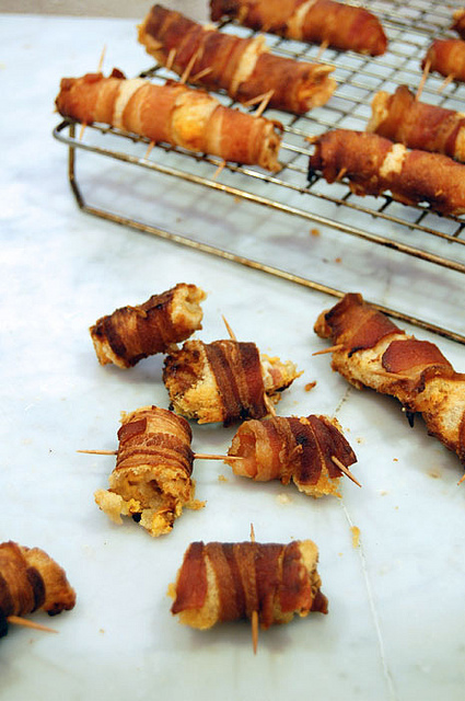 Cooked, crispy bacon wraps scattered on a white marble countertop.