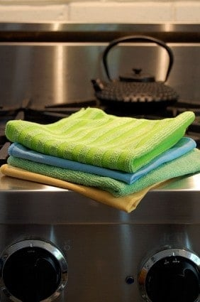 Stack of microfibre cloths on stainless steel stove.