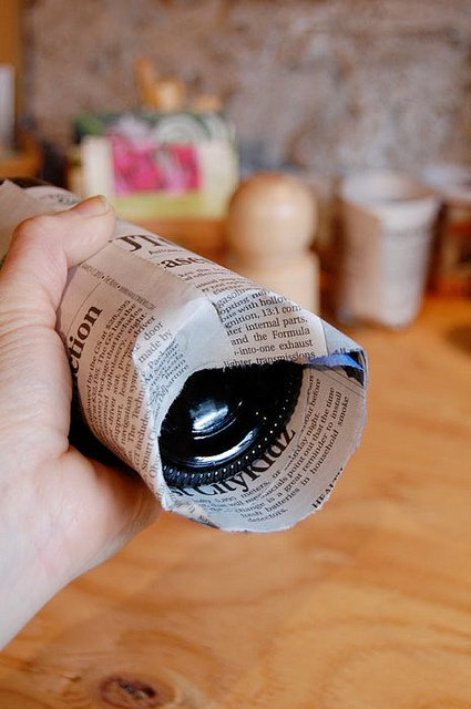 Pushing newspaper into recessed bottom of bottle.
