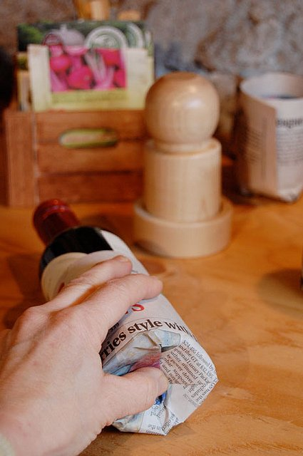 Pushing newspaper into recessed bottom of wine bottle.