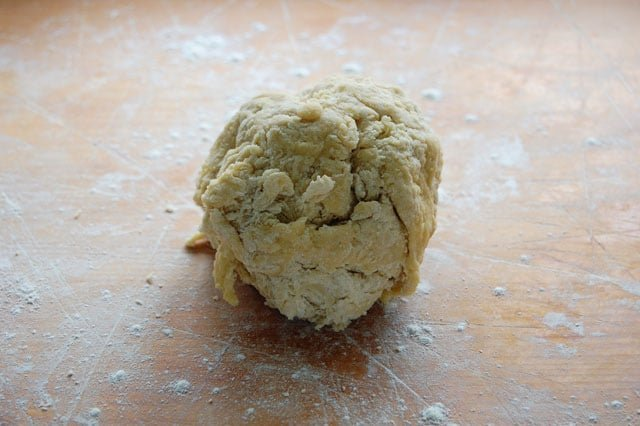 Rough ball of homemade pasta dough prior to kneading on a wood counter.