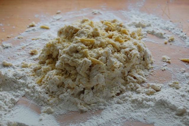 Shaggy, messy pasta dough on wood counter, just after incorporating flour and eggs.