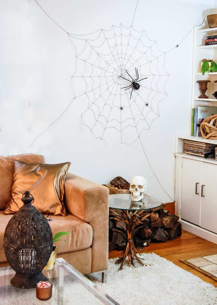 Wall sized Halloween spider web on living room wall behind taupe sofa.