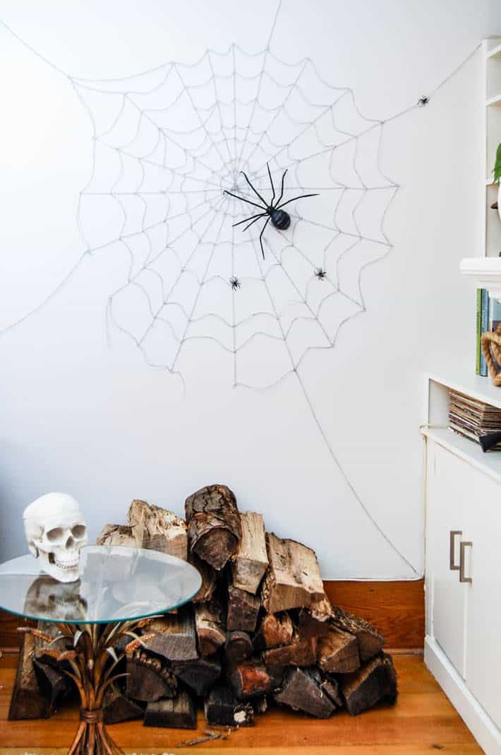 DIY spider web on wall running fro floor to ceiling over a stack of wood.