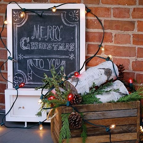 A framed chalkboard leans against a brick wall with a wood crate filed with birch logs, cedar and pinecones; old fashioned, big bulb lights intertwined around everything.