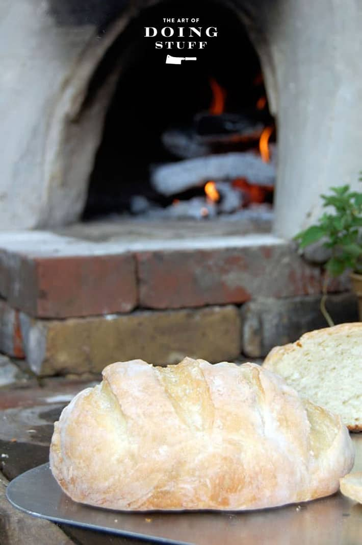 Freshly made homemade bread on hearth of brick and clay outdoor pizza oven.