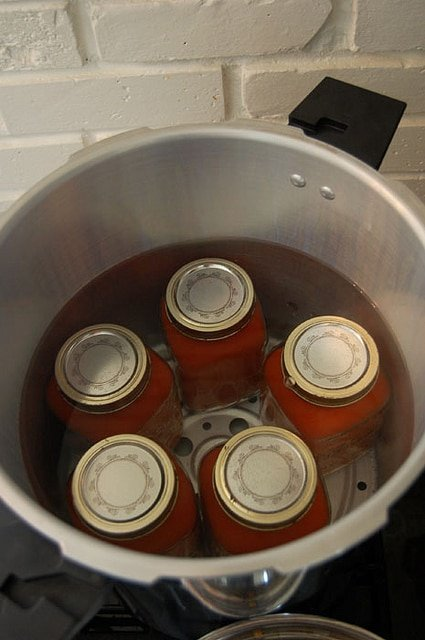 5 mason jars in a pressure canner filled with water.