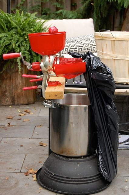 Manual tomato press clamped to a black outdoor table over a stainless steel pot in outdoor courtyard.