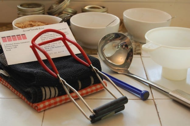 Canning tools on a white counter including tea towels, white bowls, ladles and funnels.