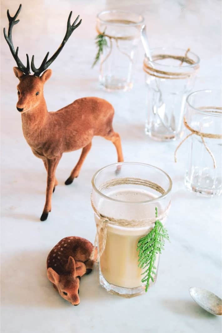 Frothy hot buttered rum in a clear pint glass with a piece of twine tied around it with a tiny cedar sprig.