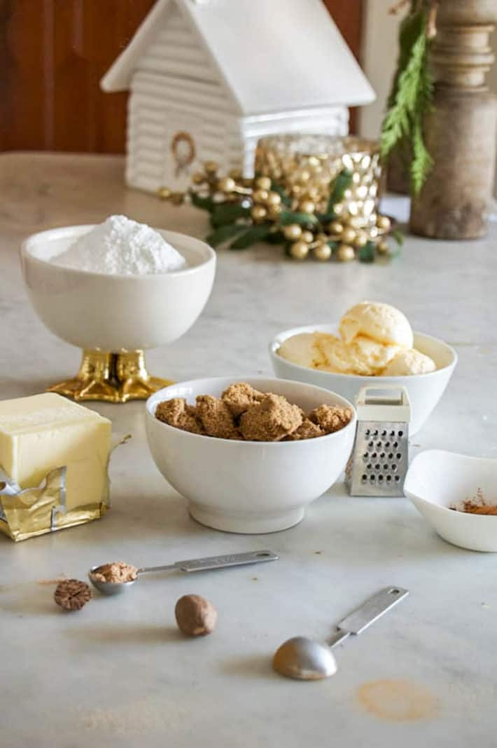 Powdered sugar in a white bowl with gold duck feet, brown sugar and vanilla ice cream in plain white bowls along with a variety of hot buttered rum spices on a marble countertop.