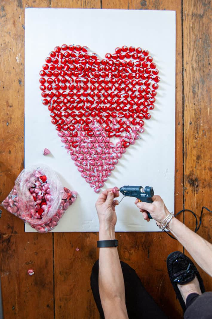 Hot gluing red and pink Hershey's kisses to board to make huge candy filled Valentine's Day card.