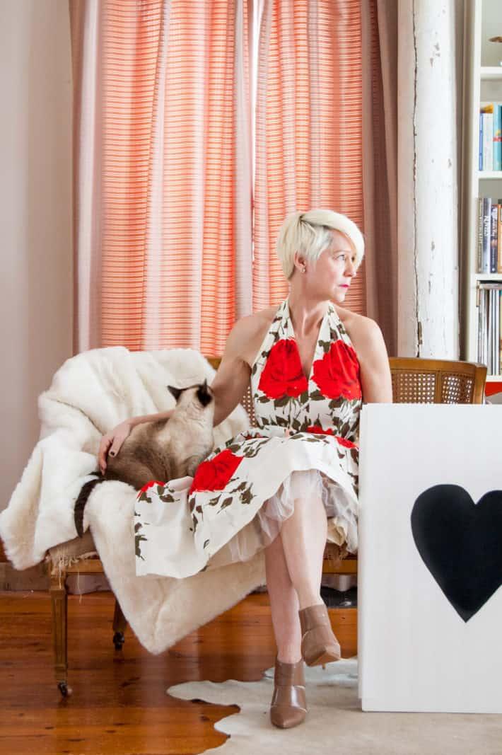 Karen Bertelsen in vintage 50's dress sitting on antique caned settee with siamese cat.