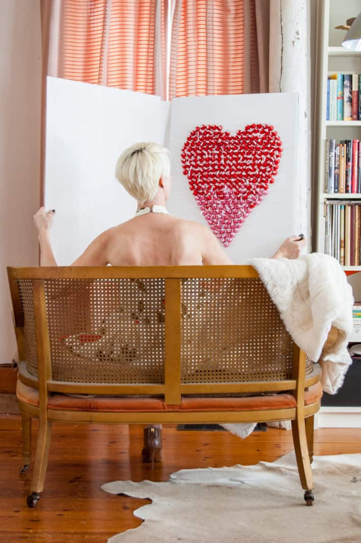 Woman with short platinum hair opening a huge Valentine's Day card made with Hershey's Kisses.